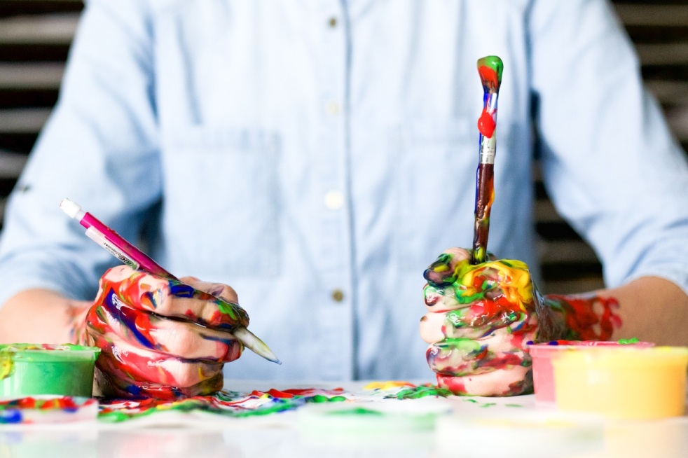Person holding messy paint and pencils